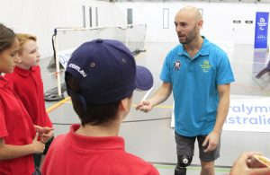 Image of Australian male Paralympian in a blue t-shirt talking to a group of 3 school children.